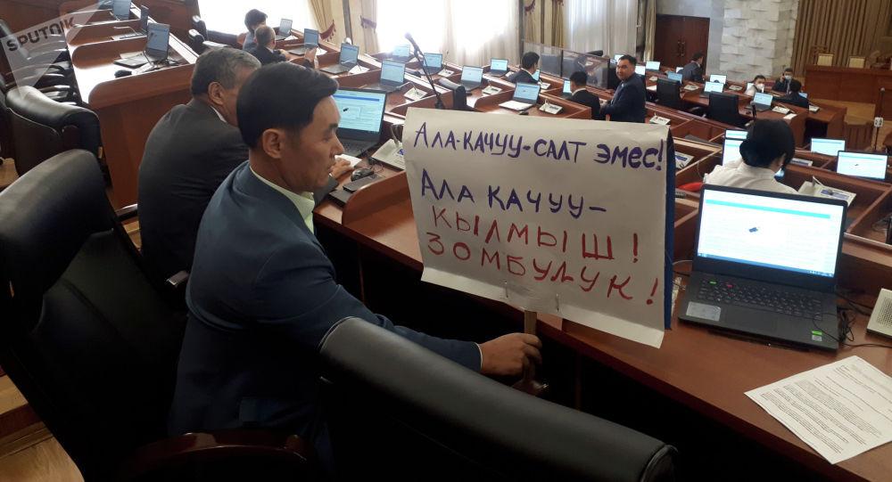Ала качуу — кылмыш! Депутат парламент жыйынына плакат көтөрүп келди